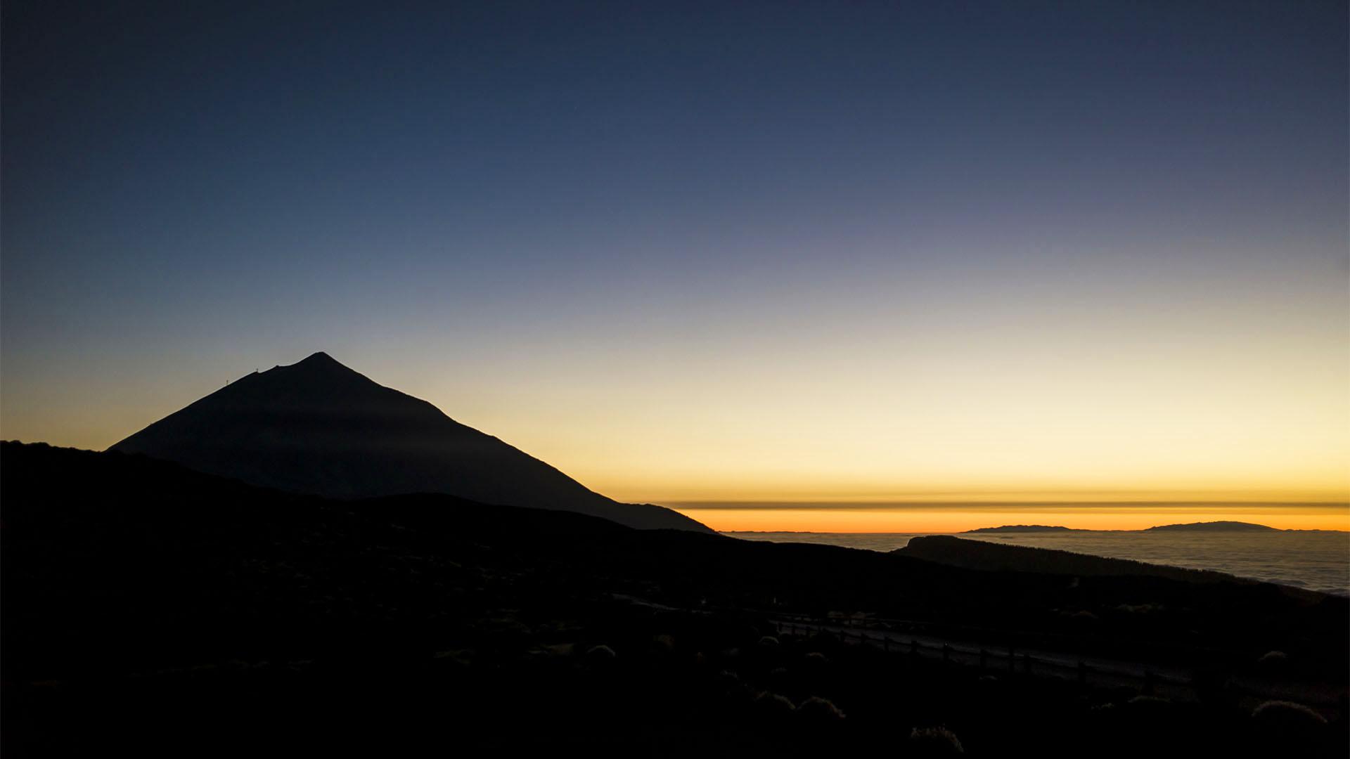 Neben der Silouhette des Teide versinkt die Sonne im Wolkenmeer aus dem die Gebirgszüge der Insel La Palma ragen. Blick vom Montaña de la Carniceria 2.367 m.